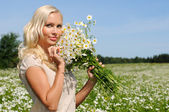 Mujer hermosa en el prado con montón de chamomiles. — Foto de Stock