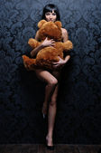 Beautiful naked girl is holding the teddy bea — Stock Photo