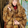 Beautiful woman in fur coat in the  luxurious classical interior. — Stock Photo