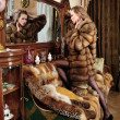 Woman in fur coat at the mirror in Luxurious classical interior. — Stock Photo