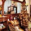 Woman in fur coat at the mirror in Luxurious classical interior. — Stock Photo #9209383