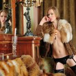 Woman in fur coat  at the mirror in  Luxurious classical interior. — Stockfoto