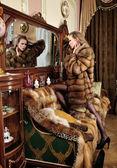 Kobieta w futra w lustrze w luksusowym wnętrzu klasycznego. — Zdjęcie stockowe