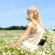 Beautiful young woman at the meadow with bunch of chamomiles. — Stock Photo