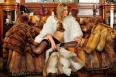 Beautiful woman in fur coat in a luxurious classical interior. — Stock Photo