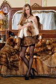 Beautiful woman in fur coat in a luxurious interior. — Stock Photo