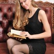 Beautiful blonde reading book on the antique sofa. — Stock Photo