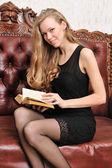 Schöne blonde Lesebuch auf dem Antik sofa. — Stockfoto