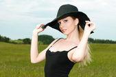 Beautiful woman in a big black hat — Stock Photo