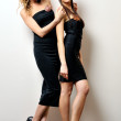 Two beautiful women in a black dresses. — Stock Photo