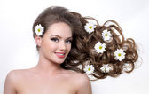 Smiling woman with camomiles in hair — Stock Photo