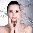 Splashes of water on the face of beautiful sexy woman — Stock Photo