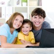 Happy family with son at home with laptop — Stock Photo