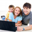 Happy family with laptop — ストック写真