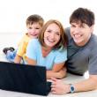 Счастливая семья с ноутбуком — Стоковое фото