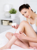Woman applying cream on her leg — Stock Photo