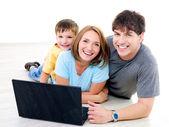 Happy family with laptop — Stock Photo
