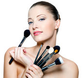 Beautiful young woman holding make-up brushes — Stock Photo