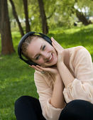 Happy woman sitting on grass listening to music outdoors and lau — Stock Photo