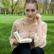 Young nice attentive woman lies on green grass and reads book — Stock Photo