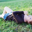 Happy young woman lying on green grass — Stock Photo