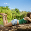 Stock Photo: Beautiful girl lying on tree in denim shorts and t-shirt loo