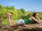 Beautiful girl lying on a tree in denim shorts and a t-shirt loo — Stock Photo