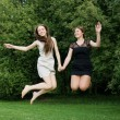 Two young cheerful women jumping — Stock Photo