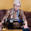 Senior womusing sewing machine at home — Stock Photo #10619595