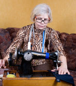 Senior woman using sewing machine at home — Stock Photo