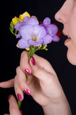 Woman sniffing flowers, freesia — Stock Photo