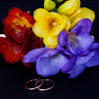 Wedding rings and a bouquet of freesias - Stock Photo