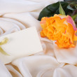 Yellow rose and a card on a gentle silk — Stock Photo