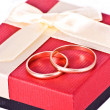Stock Photo: Golden wedding rings near red gift box
