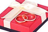 Złote obrączki ślubne w pobliżu czerwone pudełko — Zdjęcie stockowe