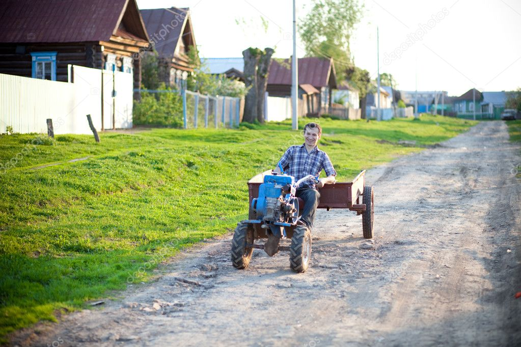 The young man goes on a tractor on the village. — Stock Photo #10651661