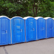 Row of blue public toilets in Moscow park - Stok fotoraf