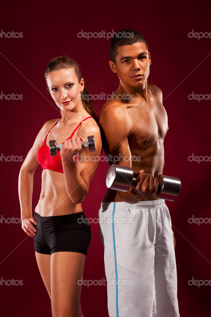 Strong young man and woman working out with dumbbells — Stock Photo #8516026