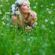 Young woman blowing a dandelion on fields — Stock Photo