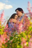 Happy Young Couple in garden of flowers — Stock Photo