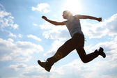 Young man jumping against cloudy sky — Stock Photo