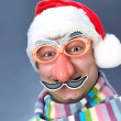 Man in a ridiculous Santa Claus mask in the warm scarf — Stock Photo