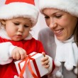 Beautiful mum with a small child open a Christmas gift — Stock Photo