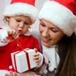 ストック写真: Beautiful mum with small child open Christmas gift
