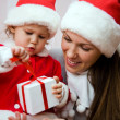 Стоковое фото: Beautiful mum with small child open Christmas gift