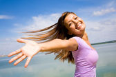 Beautiful young woman opened her hands with delight at the blue sky — Stock Photo