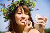 Portrait of Young beautiful woman in floral wreath uses lipstick — Stock Photo