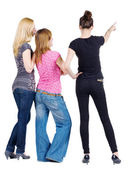Back view of group beautiful women pointing at wall. — Stock Photo