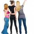 Foto Stock: Back view of group beautiful women pointing at wall