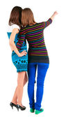 Back view of two young brunette woman pointing at wall — Stock Photo